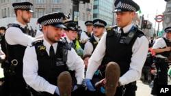 Polisi menangkap para pengunjuk rasa di Oxford Circus di London, Jumat, 19 April 2019. Kelompok Extinction Rebellion menyerukan pekan perlawanan sipil terhadap kegagalan untuk mengatasi penyebab perubahan iklim.