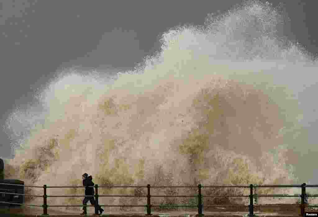 A woman is sprayed by a wave as she walks along the seafront in New Brighton, England.