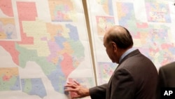 "FILE - Texas state Sen. Juan ""Chuy"" Hinojosa looks at maps on display prior to a Senate Redistricting committee hearing, in Austin, Texas, May 30, 2013."