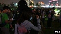 香港民眾11月9日晚在添馬公園舉行集會,悼念不幸去世的香港科技大學學生周梓樂。一對情侶相擁互勉。(美國之音鬱崗拍攝)