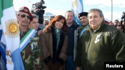 Argentina's President Cristina Fernandez de Kirchner (C) poses with Argentine war veterans during a ceremony to pay homage to the fallen soldiers during the Falklands War in Ushuaia, April 2, 2015.