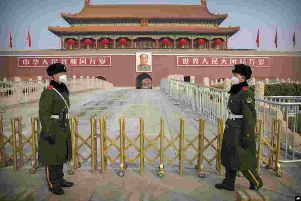 មន្រ្តីប៉ូលិសពាក់ម៉ាសឈរល្បាតនៅពីមុខក្លោងទ្វារ Tiananmen Gate ក្នុងក្រុងប៉េកាំង ប្រទេសចិន។