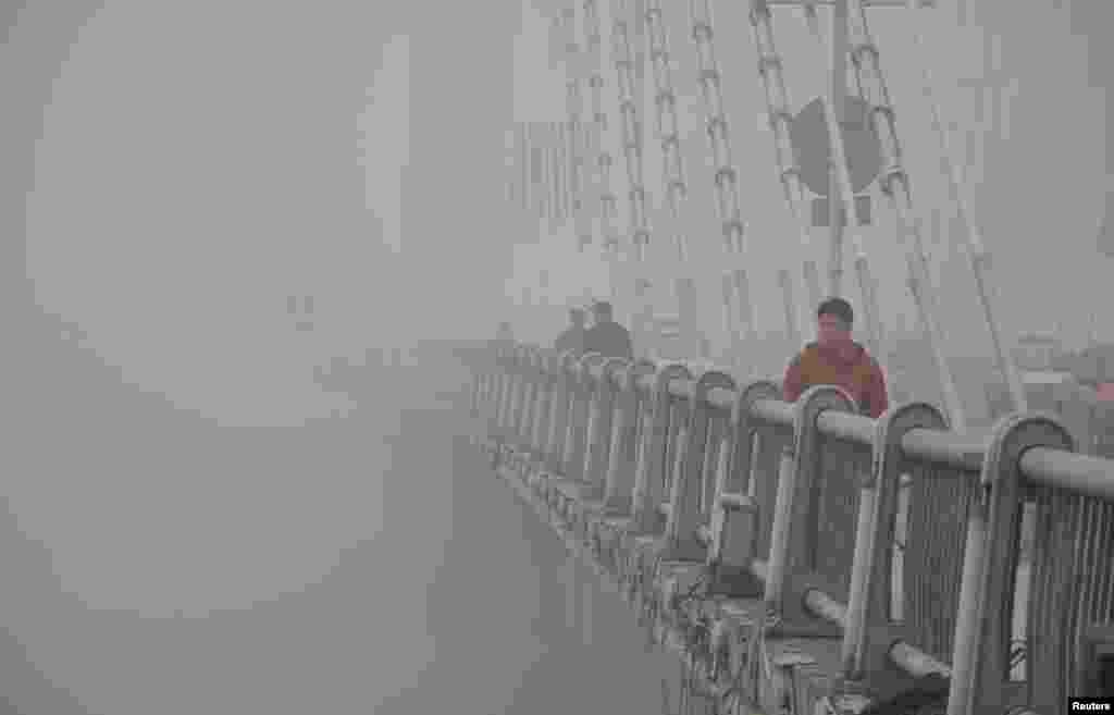 People walk on a bridge during a smoggy day in Jilin, Jilin province, Oct. 21, 2013.