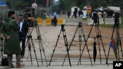 FILE - Pakistani journalists are seen at a stake-out in Islamabad, Pakistan, Nov. 6, 2013. Recently, a Pakistani government body, established to regulate private TV channels, has started asserting itself in ways that have raised concerns with media watchdogs.