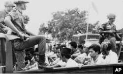 FILE - Members of the Youth Wing of the Indonesian Communist Party are guarded by soldiers as they are taken by an open truck to prison in Jakarta after they were rounded up by the army following a crackdown on communists after an attempted coup, Oct. 30, 1965.