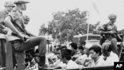 Members of the Youth Wing of the Indonesian Communist Party are guarded by soldiers as they are taken by an open truck to prison in Jakarta following a crackdown on communists in 1965.