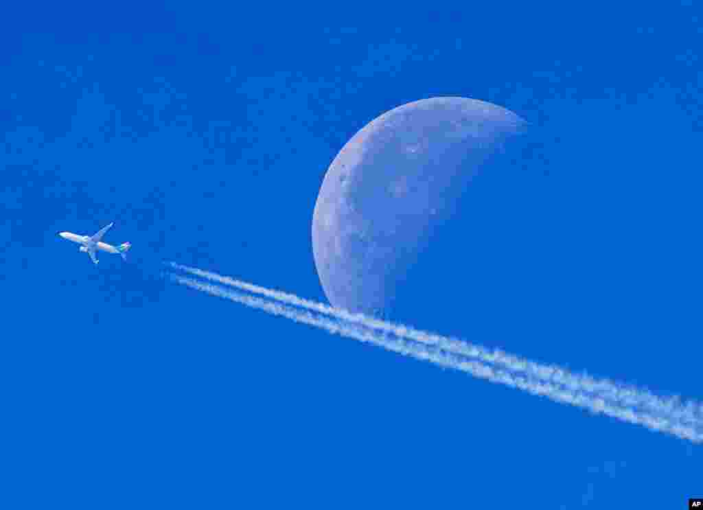 An aircraft passes the setting moon over Frankfurt, Germany.