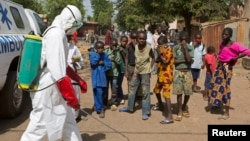 Children watch as a health worker sprays disinfectant outside a mosque in Bamako, Mali, Nov. 14, 2014.