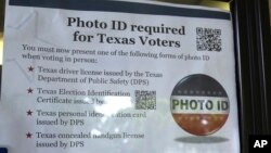FILE - A sign in a window tells of photo ID requirements for voting at a polling location in Richardson, Texas, Nov. 5, 2013. The Trump administration says Texas has rid its voter ID law of any discriminatory effects and is asking a judge who once compare