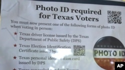 "FILE - A sign in a window tells of photo ID requirements for voting at a polling location in Richardson, Texas, Nov. 5, 2013. The Trump administration says Texas has rid its voter ID law of any discriminatory effects and is asking a judge who once compared the measure to a ""poll tax"" to not take further action."
