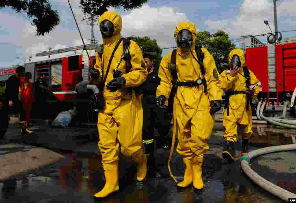 Firemen in protective suits walk near the site of an amonia leak at a cold storage unit in Baoshan district of Shanghai, China. The ammonia leak killed 15 people and sickened dozens, the city government said.