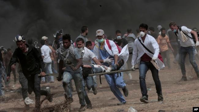امدادگران در حال انتقال معترضانی که در چهارمین هفته تظاهرات فلسطینی ها در مرزهای غزه و اسرائیل زخمی شده اند - ۳۱ فروردین ۱۳۹۷