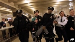FILE - Occupy Wall Street activist Lauren Digioia is detained by police during a demonstration against the National Defense Authorization Act in New York's Grand Central Station, Jan. 3, 2012.