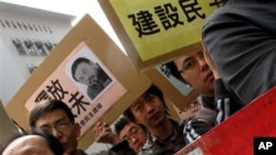 Human rights protesters hold a rally, carrying the picture of Ai Weiwei, one of its most famous contemporary Chinese artists outside the China Liaison Office in Hong Kong, April 5, 2011
