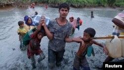 ຜູ້ຊາຍຊາວອົບພະຍົບໂຣຮິຢາຄົນນຶ່ງ ຊ່ອຍພວກເດັກນ້ອຍຍ່າງ ຜ່ານຂີ້ຕົມ ຫຼັງຈາກຍ່າງຜ່າແມ່ນ້ຳ Naf ໃນຊາຍແດນ Bangladesh ຕິດກັບມຽນມາ ໃນເມືອງ Palong Khali, ໃກ້ເມືອງ Cox's Bazar, Bangladesh, 1 ພະຈິກ, 2017.