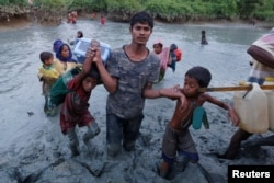 FILE - A Rohingya refugee man helps children through the mud after crossing the Naf River at the Bangladesh-Myanmar border in Palong Khali, near Cox's Bazar, Bangladesh, Nov. 1, 2017.