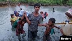 A Rohingya refugee man helps children through the mud after crossing the Naf River at the Bangladesh-Myanmar border in Palong Khali, near Cox's Bazar, Bangladesh, Nov. 1, 2017.