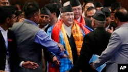 FILE - Nepal's prime minister, Khadga Prasad Oli, center, speaks with members of his cabinet inside the Constituent Assembly in Kathmandu, Nepal, Oct. 11, 2015.