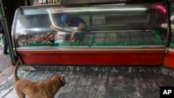 Un empleado coloca carne de cerdo en un refrigerador de una tienda en Caracas, Venezuela. Foto de archivo. Oct. 27 de 2017.