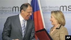 US Secretary of State Hillary Rodham Clinton, right, and Russia's Foreign Minister Sergey Lavrov smile after finalizing the New START treaty during the Conference on Security Policy in Munich, Germany, February 5, 2011