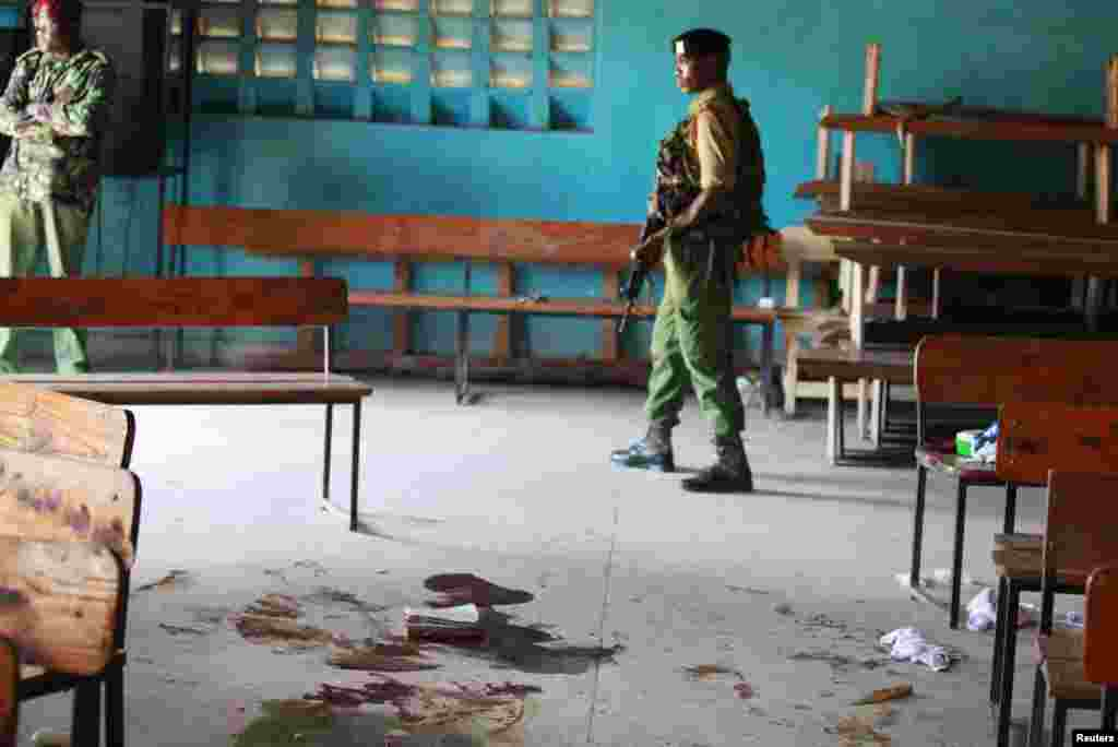 A Kenyan policeman walks past blood stains on the floor of a church after an attack by gunmen on worshippers, Mombasa, Kenya, March 23, 2014.
