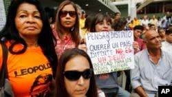 """2019年8月7日委内瑞拉加拉加斯举行的抗议活动中,一名妇女举着西班牙文标牌。上面写着""""以不同的方式思考和想要一个不同的国家不是犯罪。政治犯应有自由。"""""""