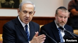 Israel's Prime Minister Benjamin Netanyahu (L) speaks during the weekly cabinet meeting in Jerusalem, May 19, 2013.