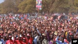 Supporters hold up a portrait of Zimbabwe Prime Minister Morgan Tsvangirai at his last campaign rally before elections set for Wednesday, in Harare, July 29, 2013.