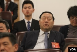 A delegate at Chinese People's Political Consultative Conference takingb a nap.