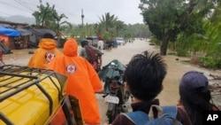 Para suka relawan dan warga melintasi jalan yang banjir akibat topan Conson di desa Usab, provinsi Masbate, Filipina tengah, Selasa 7 September 2021. (Palang Merah Filipina via AP)