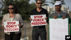 Israeli Arab supporters of Mohammed Allan, a Palestinian prisoner on a hunger strike, hold signs during a support rally, in Ashkelon Israel, Aug. 11, 2015.