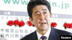 ອະດີດນາຍົກ ລັດຖະມົນຕີ Shinzo Abe ຜູ້ນໍາພາພັກພັກເສລີປະຊາທິປະໄຕ ຫຼື LDP ຊຶ່ງເປັນພັກຝ່າຍຄ້ານໃຫຍ່ໃນຍີ່ປຸ່ນ ຢືນຢູ່ຕໍ່ໜ້າກະດານປະກາດຜົນເລືອກຕັ້ງ ທີ່ສໍານັກງານຂອງພັກ LDP ທີ່ກຸງໂຕກຽວ ໃນວັນທີ 16 ທັນວາ 2012.