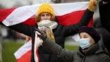 Жінка з червоно-білим прапором на протесті у неділю у Мінську.