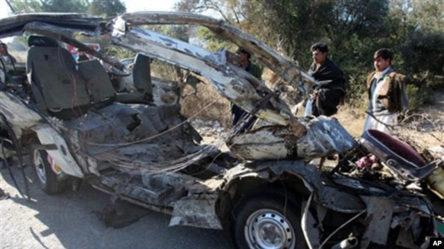 People look at the remains of a passenger minibus near Hungu in Pakistan's northwest province, 17 Jan 2011.
