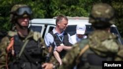 Anggota tim pemantau Uni Eropa (OSCE) Alexander Hug (tengah) dikawal oleh separatis pro-Rusia di Ukraina timur (30/7)