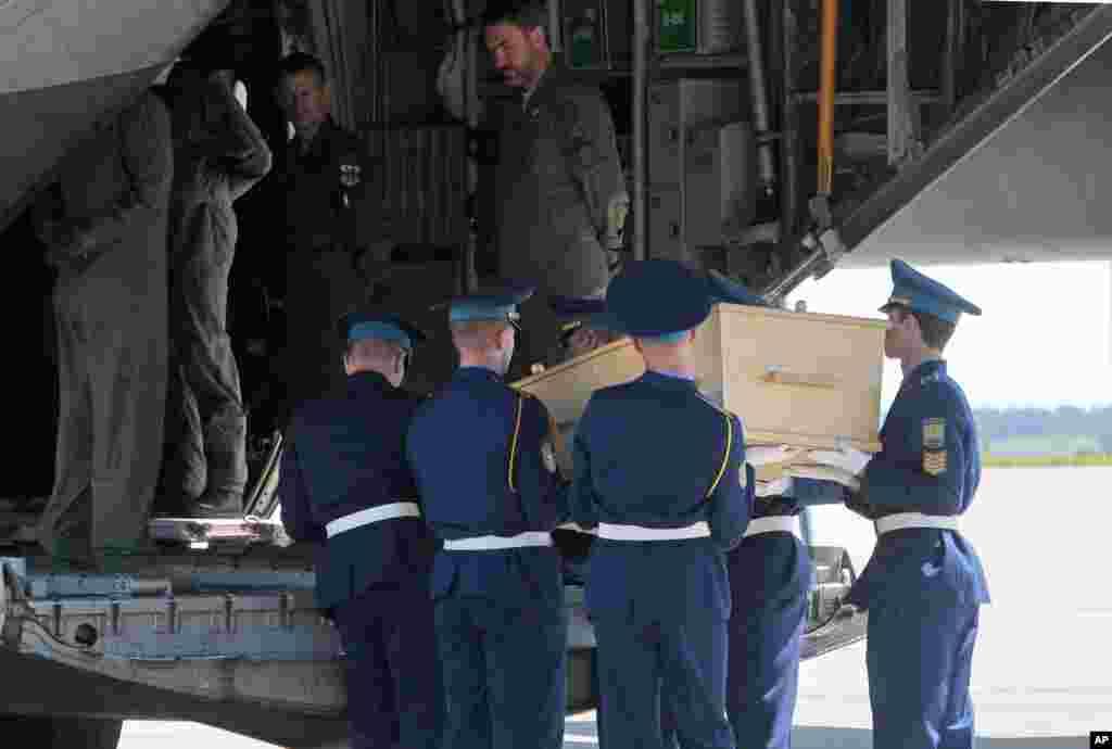 우크라이나 크하르키브 공항에서 우크라이나 의장대가 말레이시아 여객기 희생자 시신을 네델란드행 수송기에 싣고 있다.