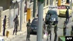Hình ảnh từ video do hãng tin Ugarit phát hành ngày 7/8/2011 cho thấy binh sĩ Syria đứng cạnh thi thể của một người đàn ông ở thị trấn Idlib ở phía bắc Syria