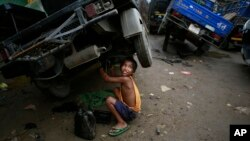 Biswa Gurung, a seven-year-old Indian boy talks to a colleague as he works at an automobile workshop in Gauhati, India, Oct. 12, 2014