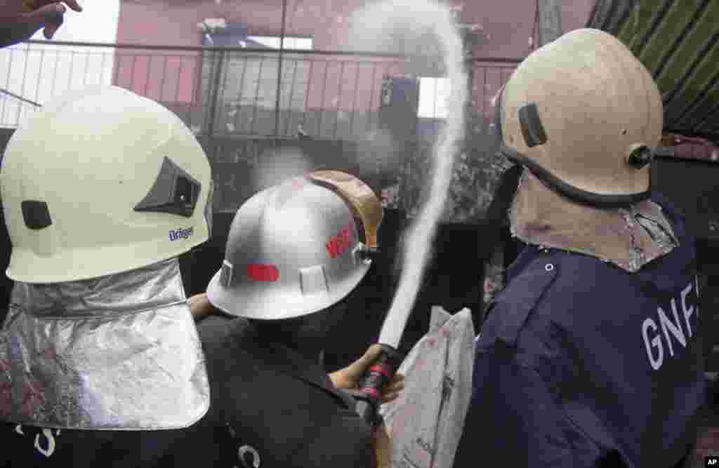Bombeiros pulverizam água sobre uma estrutura remanescente de um posto de gasolina depois que explodiu em Acra, Gana, Quinta-feira, 4 de Junho, 2015.