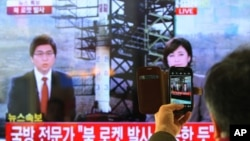 South Korean man uses his smartphone to take a photo of television screen reporting news about North Korea's rocket launch at Seoul Railway Station in Seoul, South Korea, December 12, 2012.