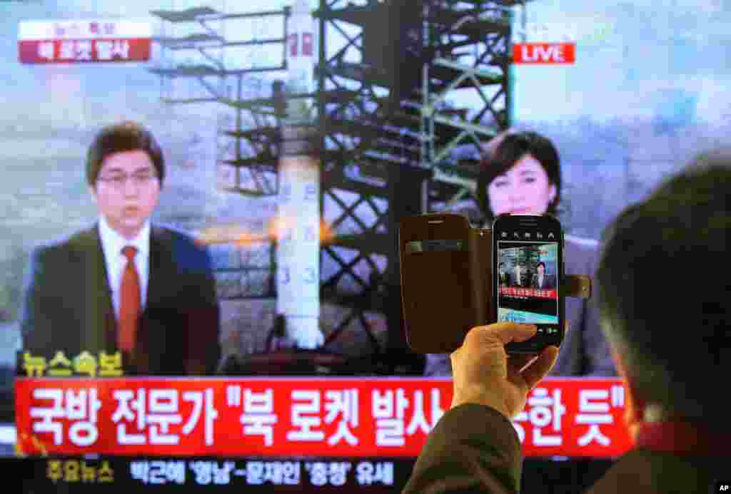 South Korean man uses his smartphone to take a photo of television screen reporting news about North Korea's rocket launch at Seoul Railway Station in Seoul, South Korea, Dec. 12, 2012.