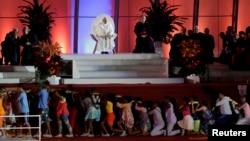 Paus Fransiskus (duduk di panggung) menyaksikan pertunjukan drama komedi yang digelar dalam perayaan Hari Pemuda Dunia di pantai Copacabana di Rio de Janeiro, di hari keempat kunjungan selama seminggunya di Brazil (25/7).