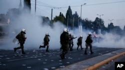 Polisi mengejar para demonstran dalam bentrokan di depan gedung parlemen di Athena (8/5). (AP/Yorgos Karahalis)