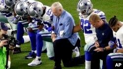 El dueño de los Cowboys, Jerry Jones (centro) hincado junto con los jugadores antes del himno nacional, en Glendale, Arizona.
