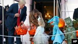 Presiden AS Donald Trump dan ibu negara Melania Trump membagikan permen kepada anak-anak dalam rangka perayaan Halloween di Gedung Putih, Senin (30/10).