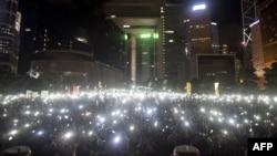 Para demonstran melambaikan ponsel dan alat elektronik lain saat melakukan protes pro-demokrasi di kompleks pemerintahan Hong Kong (31/8). (AFP/Alex Ogle)
