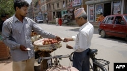 FILE - A vendor (L) exchanges money with a customer as he sells apples off his pushbike on the roadside in Lalitpur, south of Kathmandu, Nepal.