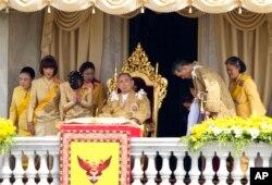 FILE - Thai King Bhumibol Adulyadej, center, is surrounded by his family members, left to right, Princess Somsavali, his daughter Princess Ubolratana, his daughter Princess Chulabhorn, Princess Siribhachudabhorn, Royal Consort Princess Srirasm, his grandson Prince Dipangkorn Rasmijoti, his son Crown Prince Vajiralongkorn and his daughter Princess Sirindhorn after addressing the crowd from a balcony of the Ananta Samakhom Throne Hall on his 85th birthday in Bangkok, Dec. 5, 2012.