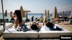 Turis berjemur di pantai kota Laut Merah, Eilat, salah satu tempat liburan populer di Israel.