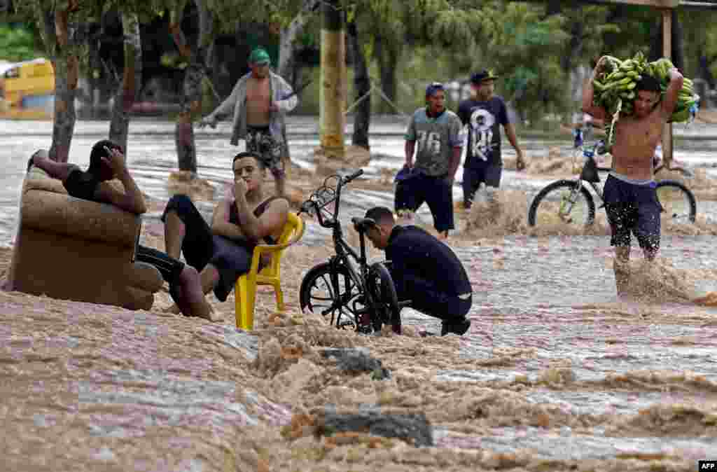 A young man carries bananas as he wades through a flooded street in El Progreso, department of Yoro, Honduras, Nov. 18, 2020, after the passage of Hurricane Iota, now downgraded to tropical storm.